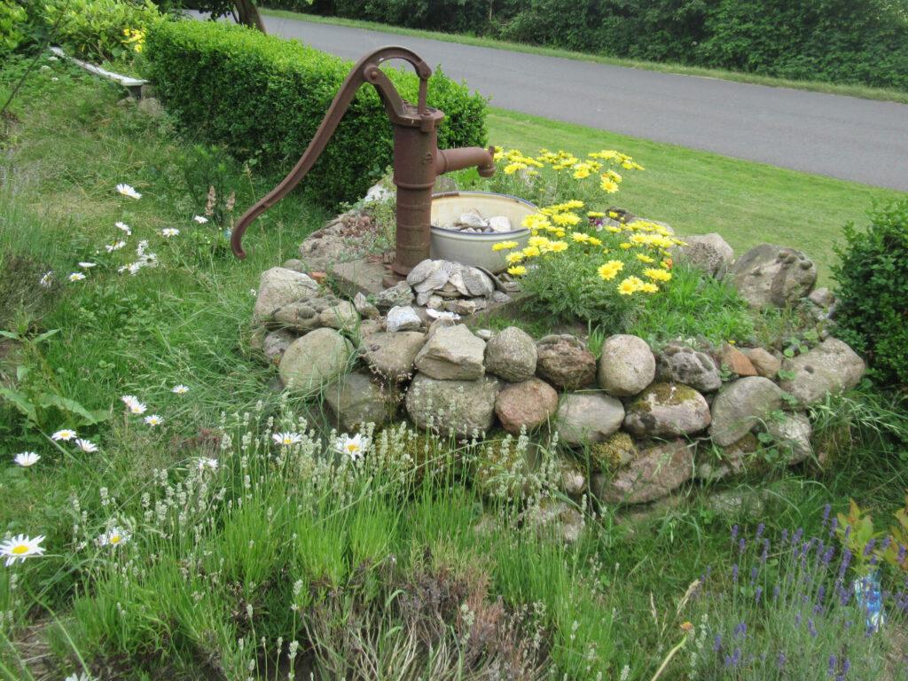 Eine alte Gartenpumpe als Dekoration im Garten